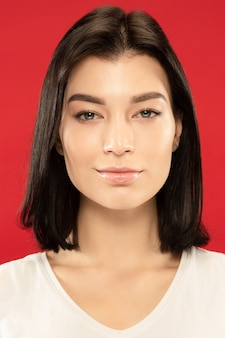 Caucasion młodej kobiety bliska portret na czerwonej ścianie