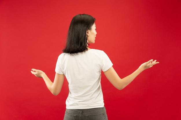Caucasion młodej kobiety w połowie długości portret na czerwonym tle studio. piękna modelka w białej koszuli. pojęcie ludzkich emocji, wyraz twarzy. pokazuje i wskazuje coś.