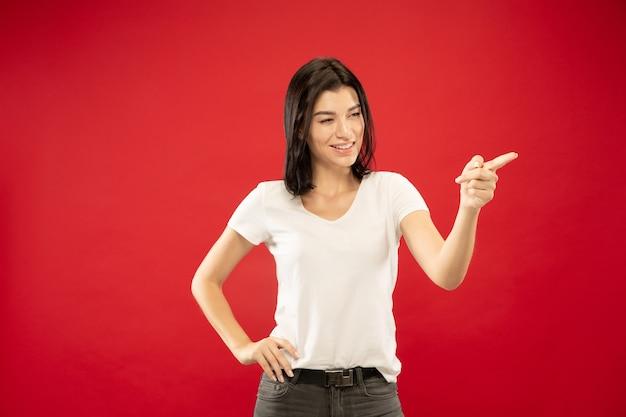 Caucasion młodej kobiety w połowie długości portret na czerwonym tle studio. piękna modelka w białej koszuli. pojęcie ludzkich emocji, wyraz twarzy. pokazywanie, wskazywanie czegoś, wygląda figlarnie.