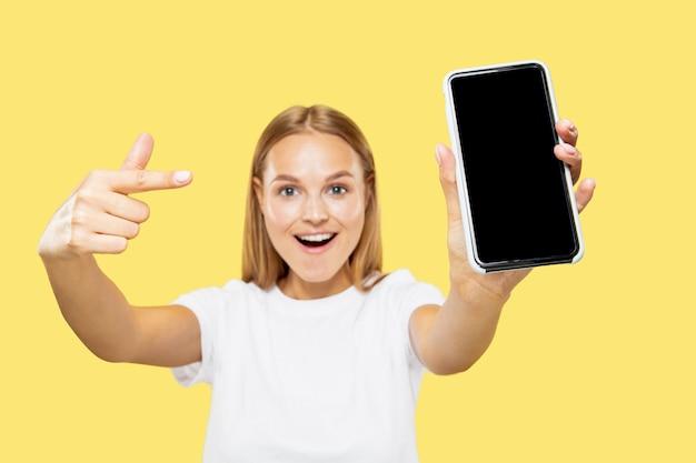 Caucasion młodej kobiety w połowie długości portret na żółtym tle studio. piękna modelka w białej koszuli. pojęcie emocji, wyraz twarzy, sprzedaż, płatność online. wyświetlam ekran telefonu.