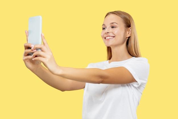 Caucasion młodej kobiety w połowie długości portret na żółtym tle studio. piękna modelka w białej koszuli. pojęcie ludzkich emocji, wyraz twarzy. uśmiechanie się, tworzenie treści selfie lub vloga.