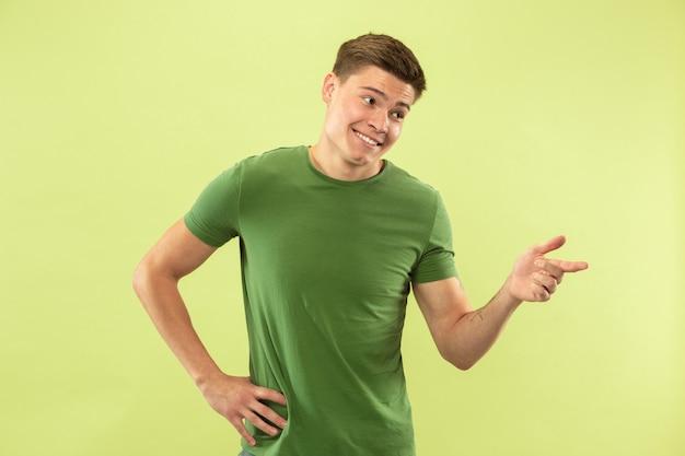 Caucasion młody człowiek w połowie długości portret na zielonym tle studio. piękny męski model w koszuli. pojęcie ludzkich emocji, wyraz twarzy, sprzedaż, reklama. wskazując, wygląda pewnie.