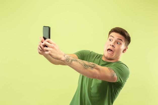 Caucasion młody mężczyzna w połowie długości portret na zielonym tle studio. piękny męski model w koszuli. pojęcie ludzkich emocji, wyraz twarzy, sprzedaż, reklama. robienie selfie lub treści do swojego vloga.