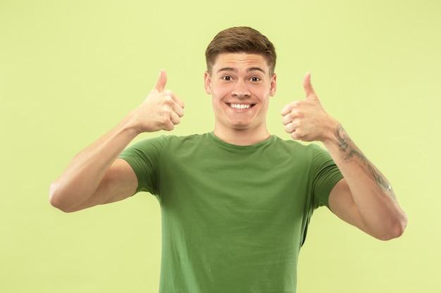 Caucasion młody mężczyzna w połowie długości portret na zielonym tle studio. piękny męski model w koszuli. pojęcie ludzkich emocji, wyraz twarzy, sprzedaż, reklama. uśmiechnięty, pokazujący kciuki do góry.