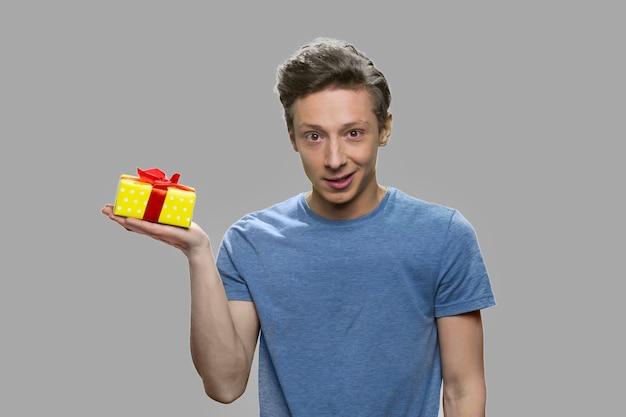 Caucasion teen boy gospodarstwa małe żółte pudełko. nastoletni facet trzyma pudełko na dłoni na szarym tle.