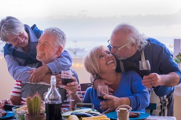 Causasian starsze pary przyjaciół bawią się razem podczas wieczornej kolacji. całować i przytulać i uśmiechać się i śmiać się na wielką koncepcję stylu życia na emeryturze. na zewnątrz na tarasie z widokiem na ocean. wino i jedzenie?