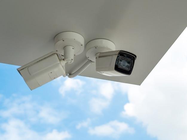 Cctv jest zainstalowany pod balkonem budynku na tle błękitnego nieba. cctv do monitorowania bezpieczeństwa.