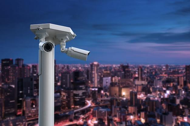 Cctv kamera bezpieczeństwa z pejzażem miejskim przy nocą