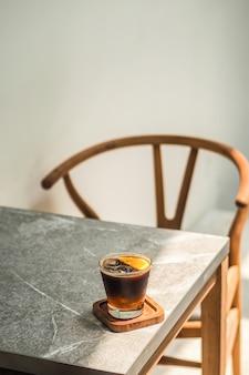 Ce kawa americano z pomarańczą na stole