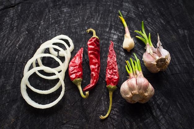 Cebula, czerwona papryka i czosnek na ciemnym stole