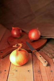 Cebula i plastry na drewnianej desce do krojenia. cebula przy drewnianym stole