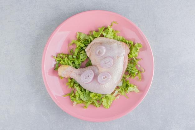 Cebula, mięso i warzywa na talerzu, na białej powierzchni