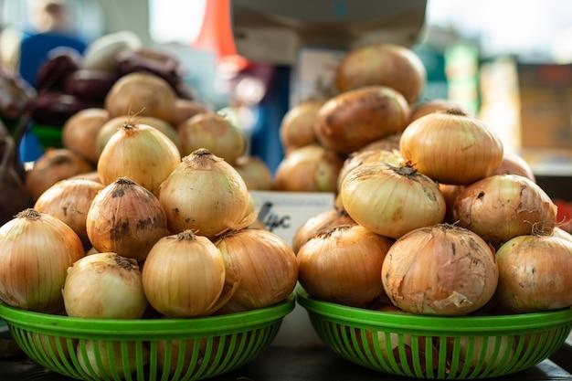 Cebule cebuli w zielonych koszyczkach.