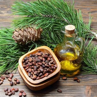 Cedrowe szyszki, orzechy i olej z orzechów cedrowych w przezroczystej butelce na drewnianym stole
