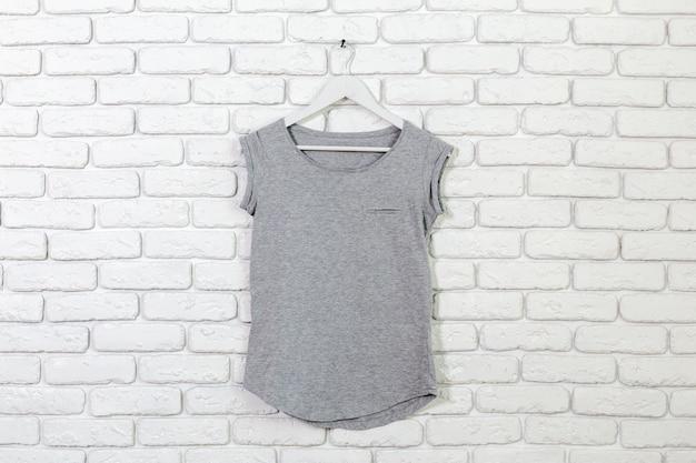 Ceglana bielona ściana z koszulką na wieszaku