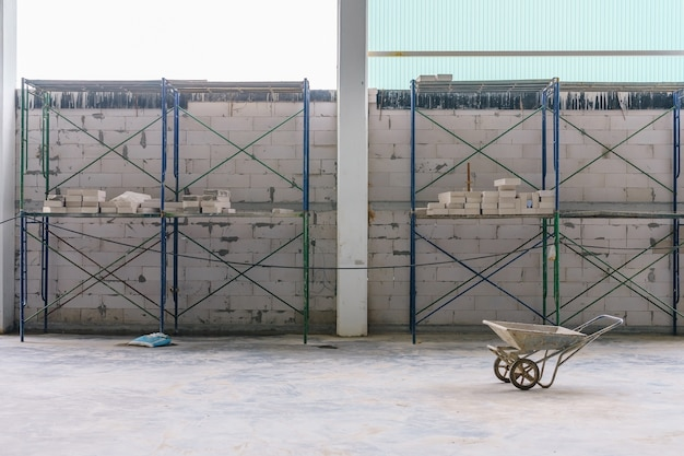 Ceglana ściana i stalowe rusztowanie dla pracownika obecnie w budowie budynku