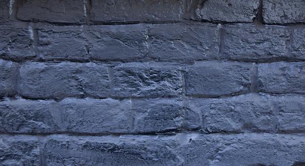 Ceglany mur pomalowany na niebiesko. tło starego rocznika błękitny ściana z cegieł. niebieski mur z cegły. latarnia uliczna ciemnoniebieski mur z cegły