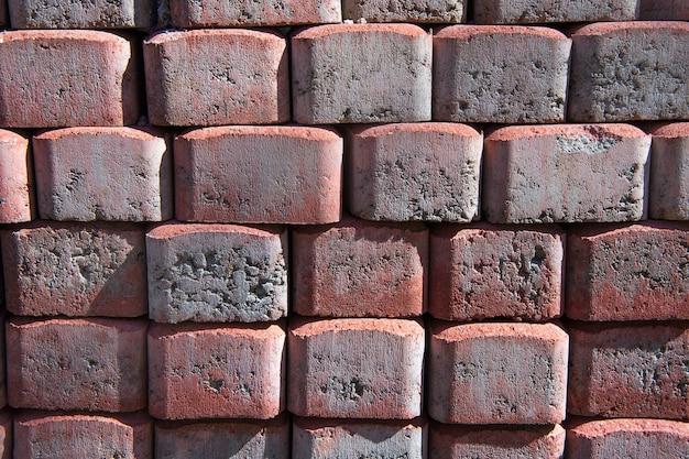 Cegły do kostki brukowej ułożone w stosy, struktura tekstury tła. materiał konstrukcyjny.
