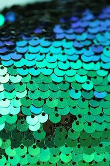 Cekiny niebiesko-zielone tło makro. morskie opalizujące łuski. błyszczący materiał. tkanina w zimnych kolorach. skala tekstur z cekinami. błyszczący materiał cekinowy