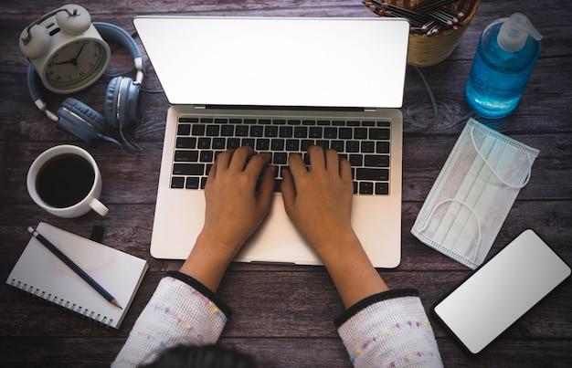 Cel i cel pracuje w domu pojęcie, odgórny widok ręka pisać na maszynie na notatniku na stole kobieta. laptop i telefon, miejsce na tekst
