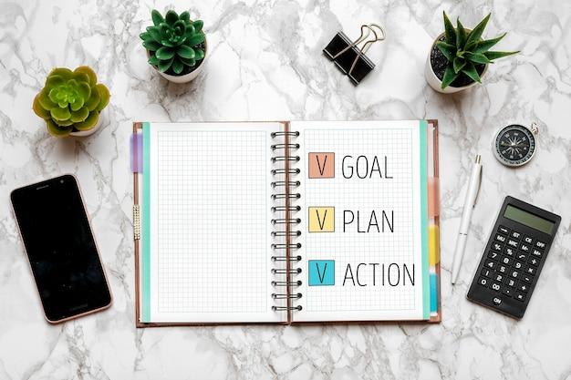 Cel na nowy rok 2021, plan, tekst działania na otwartym notatniku, okulary, filiżanka kawy, długopis, smartfon