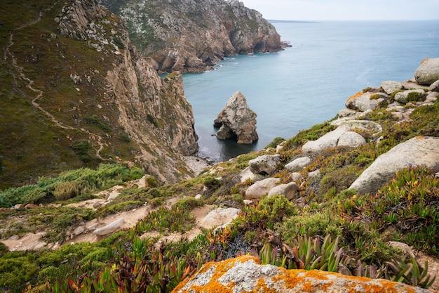 Cel podróży cabo da roca znajduje się w sintrze w portugalii. ukryta kamienista, szorstka plaża otoczona