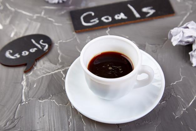 Cele jako notatka na notatniku z pomysłem, zmięty papier, filiżanka kawy