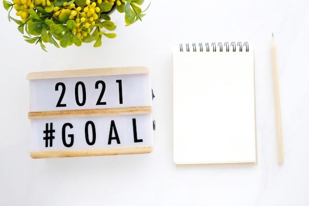 Cele na 2021 rok na drewnianym pudełku i czysty notatnik na białym tle marmuru