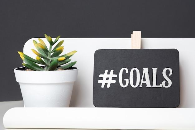 Cele na blackboard na ołówkowym pudełku i zielonej roślinie w białym garnku na stole