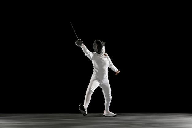 Cele. nastoletnia dziewczyna w stroju szermierki z mieczem w ręku na czarnym tle