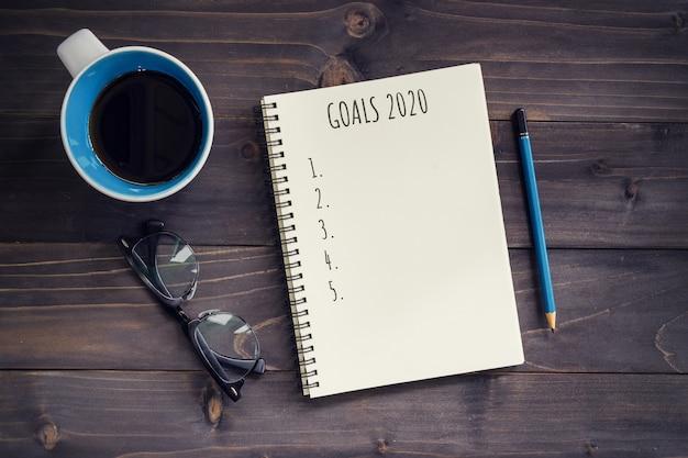 Cele nowego roku, rezolucja lub plan działania 2020. biurowy stół z drewna z pustym notatnikiem, ołówkiem, szklankami, telefonem i filiżanką kawy.