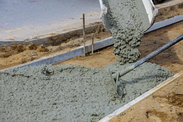 Cement przed chodnikiem nowy budynek w trakcie budowy pracownik nawierzchni betonowej na nowym chodniku
