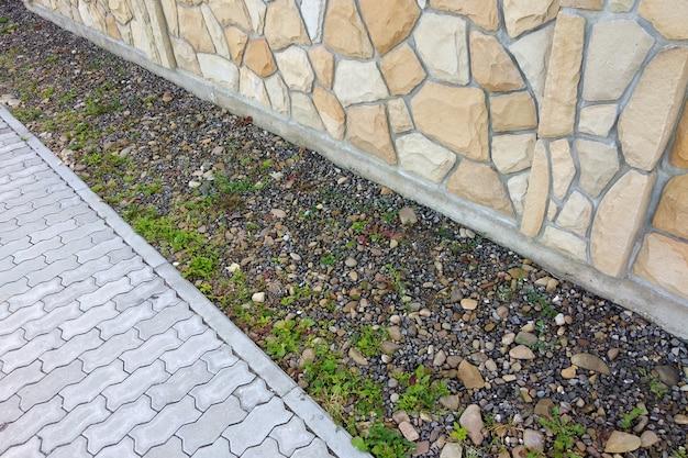 Cementowa płyta chodnikowa w pobliżu ogrodzenia lub ściany z kamienia naturalnego.