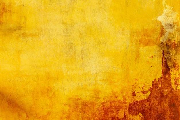 Cementowa ściana pomalowana na brązowo-żółto-pomarańczowo i czerwono na backround