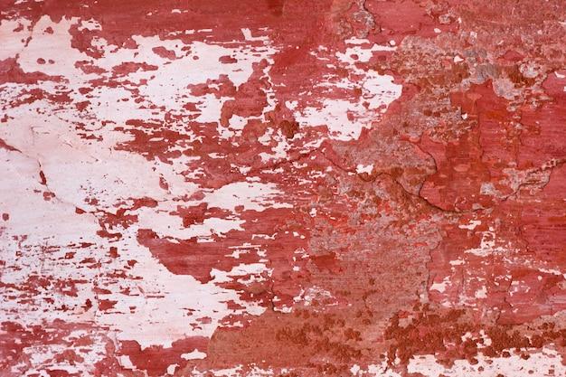 Cementowa ściana z czerwoną farbą, szorstki tło. abstrakta betonowy tło z starej obieranie czerwoną farbą.