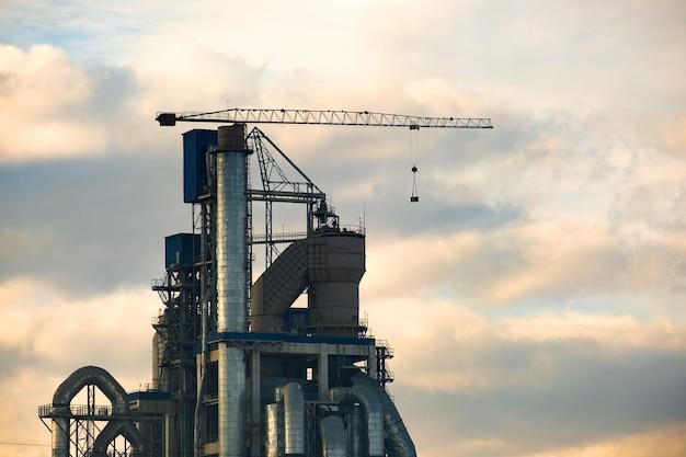 Cementownia z wysoką konstrukcją fabryczną i dźwigiem wieżowym na terenie produkcji przemysłowej.