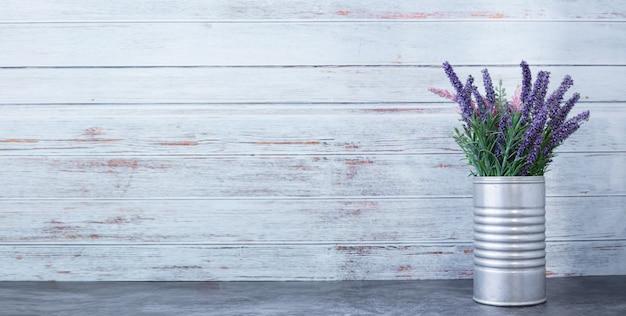 Cementowy stół z purpurowym kwiatkiem na doniczce.
