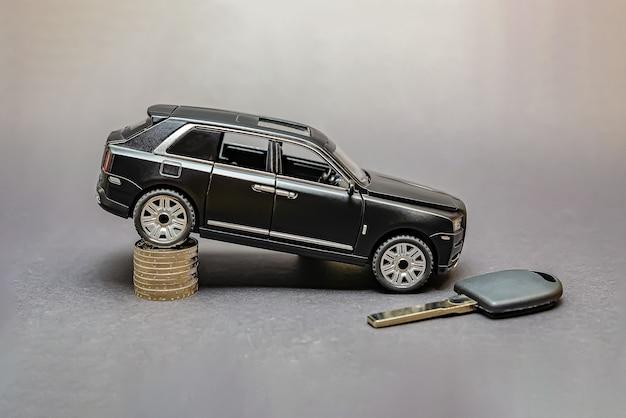 Cena samochodu. koszt części samochodowych. na czarnym tle model samochodu. wokół monety. koncepcja rozwoju rynku transportowego i cen samochodów