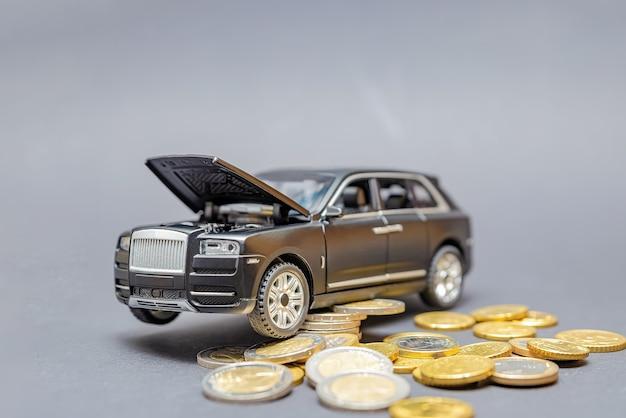 Cena samochodu. koszt części samochodowych. na czarnym tle model samochodu z podniesioną maską, wokół monety. koncepcja wzrostu cen usług samochodowych. skopiuj miejsce