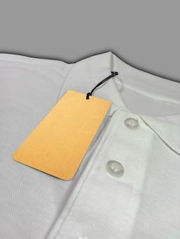 Cena tagu na białej koszulce polo na szarym tle