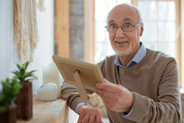 Cenna pamięć. przystojny elegancki starszy mężczyzna niosący ramkę na zdjęcia w okularach i patrząc na kamery
