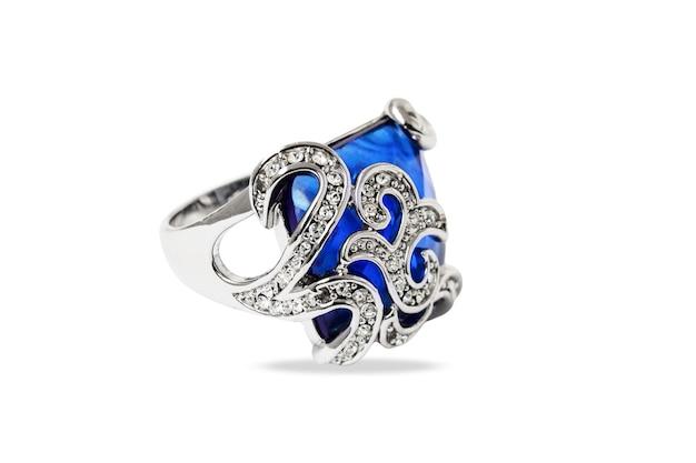 Cenny biały metalowy pierścionek z niebieskim kamieniem i małymi diamentami, zbliżenie, na białym tle