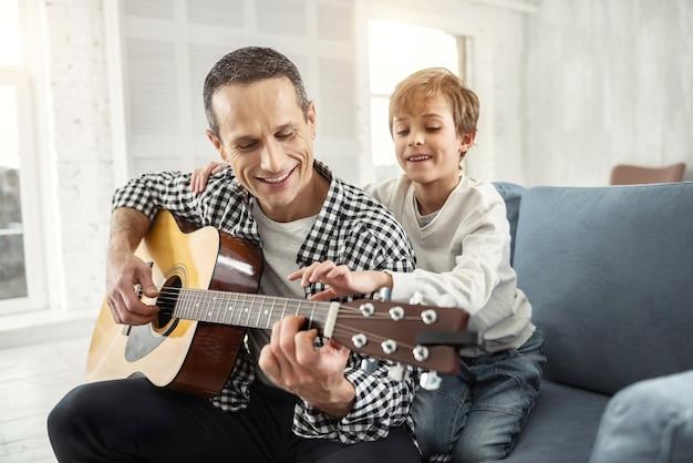 Cenny czas. przystojny radosny ciemnowłosy uśmiechnięty i grający na gitarze mężczyzna oraz jego syn siedzący za nim na kanapie