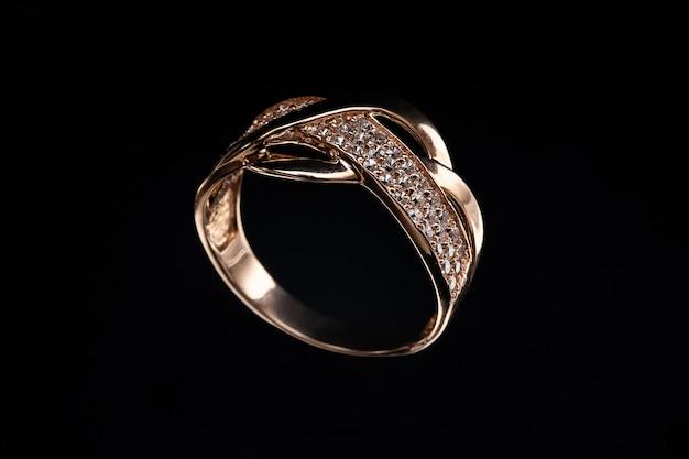 Cenny złoty pierścionek z kamieniami i odbiciem na szkle