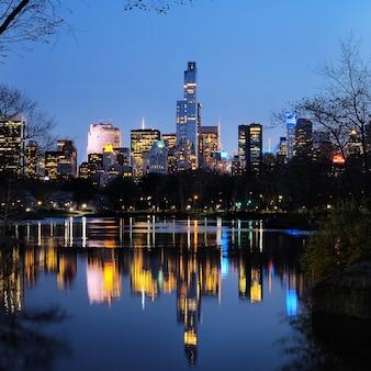 Central park w zmierzchu i odbicie budynków w centrum manhattanu nowy jork