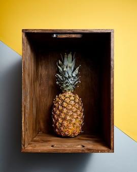 Centralna kompozycja z tropikalnym owocem ananasa w drewnianym pudełku na żółto-szarym tle. widok z góry.