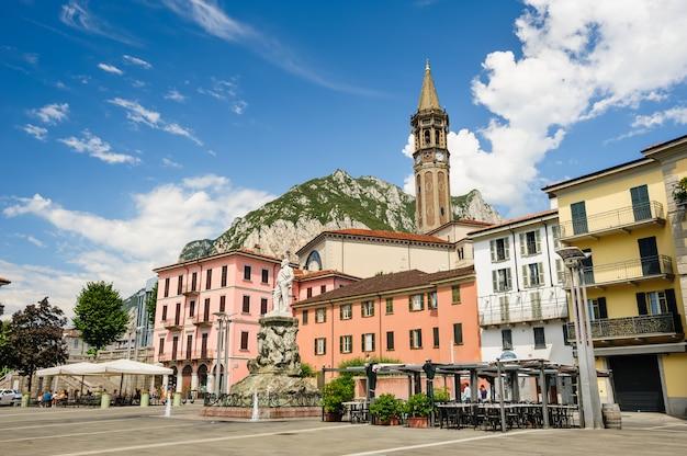 Centralne ulice miasta lecco, z kawiarnią i dzwonnicą. pomnik mario cermenati na pierwszym planie