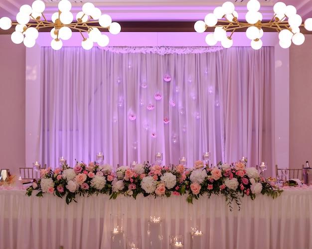Centralny stół weselny ozdobiony luksusową girlandą z kwiatów