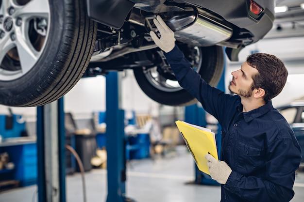 Centrum napraw samochodów. mechanik bada samochód
