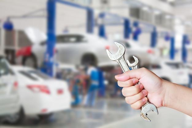 Centrum obsługi samochodów i ręka pracownika z kluczem